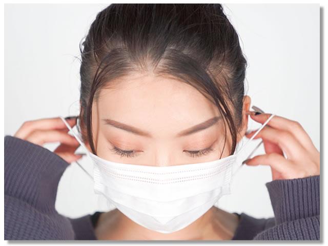 感染予防のためにマスクの正しいつけ方をする女性